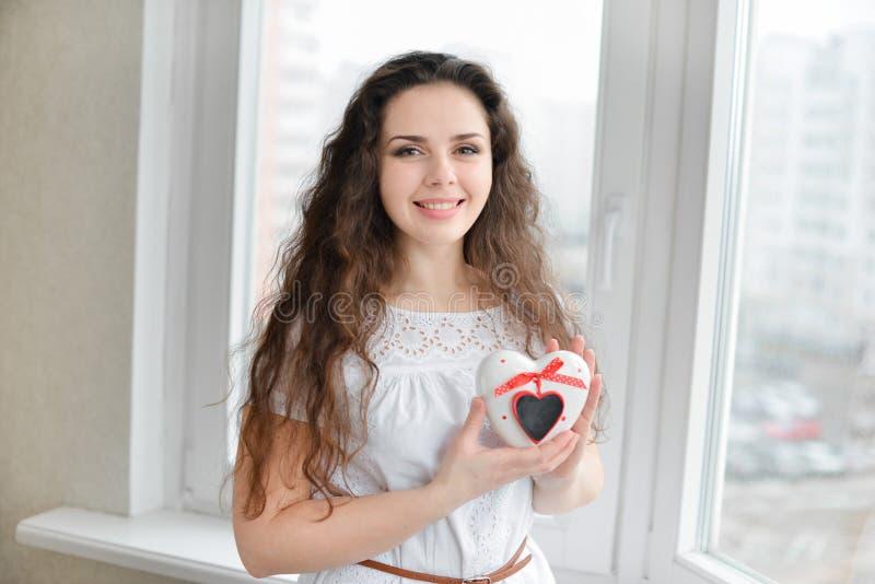 Mulher bonita no amor que prende caixa heart-shaped fotografia de stock