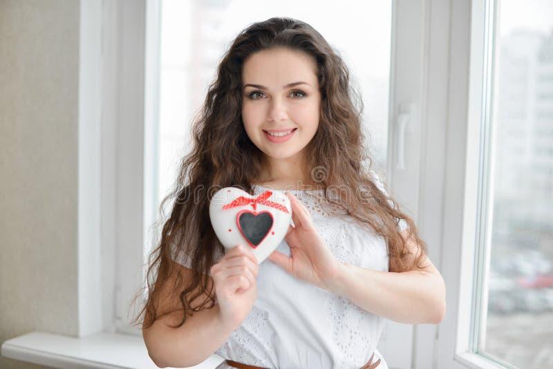 Mulher bonita no amor que prende caixa heart-shaped imagem de stock royalty free