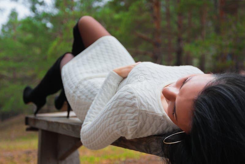 Mulher bonita no banco no parque fotografia de stock