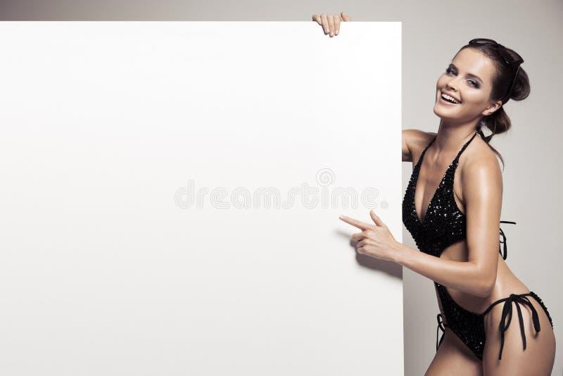 Mulher bonita no biquini que guarda o quadro de avisos branco vazio grande fotografia de stock royalty free