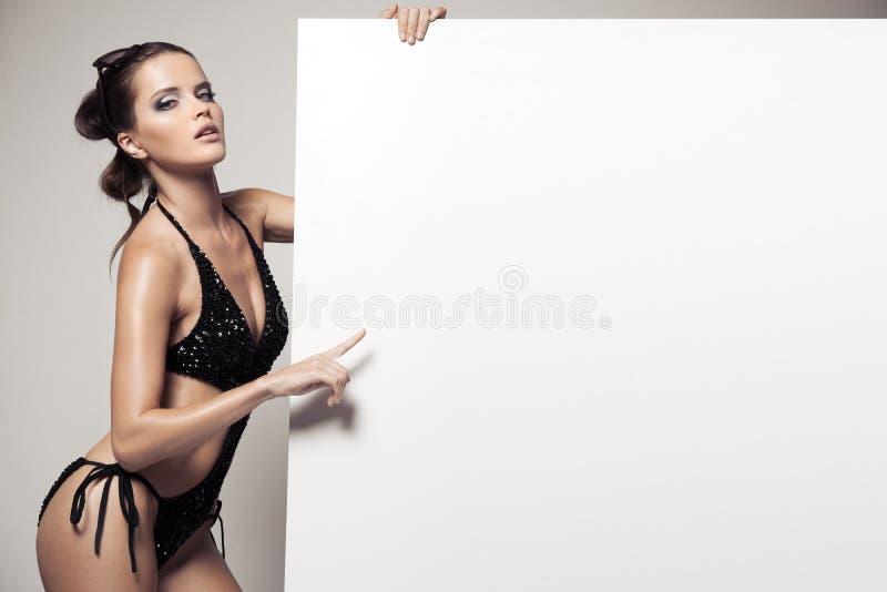 Mulher bonita no biquini que guarda o quadro de avisos branco vazio grande imagem de stock royalty free