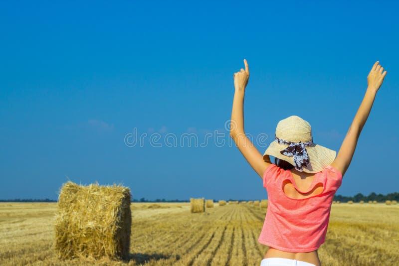 Mulher bonita no campo de trigo colhido em agosto em um dia ensolarado fotografia de stock royalty free