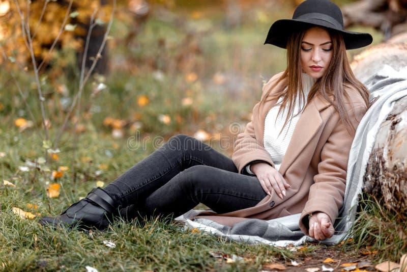 Mulher bonita no chapéu negro que senta-se sob a árvore grande fotografia de stock