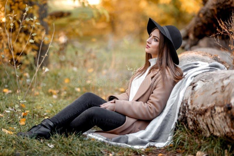 Mulher bonita no chapéu negro que senta-se sob a árvore grande fotografia de stock royalty free