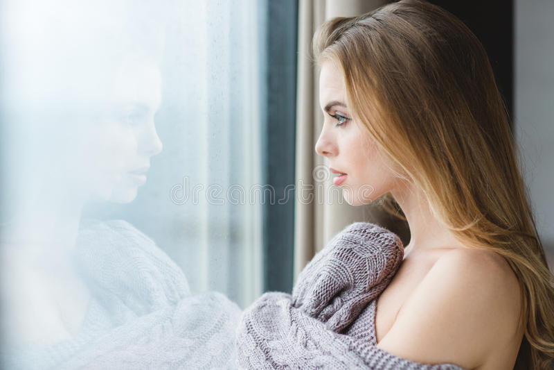 A mulher bonita no cinza fez malha a coberta que olha fora da janela imagem de stock royalty free