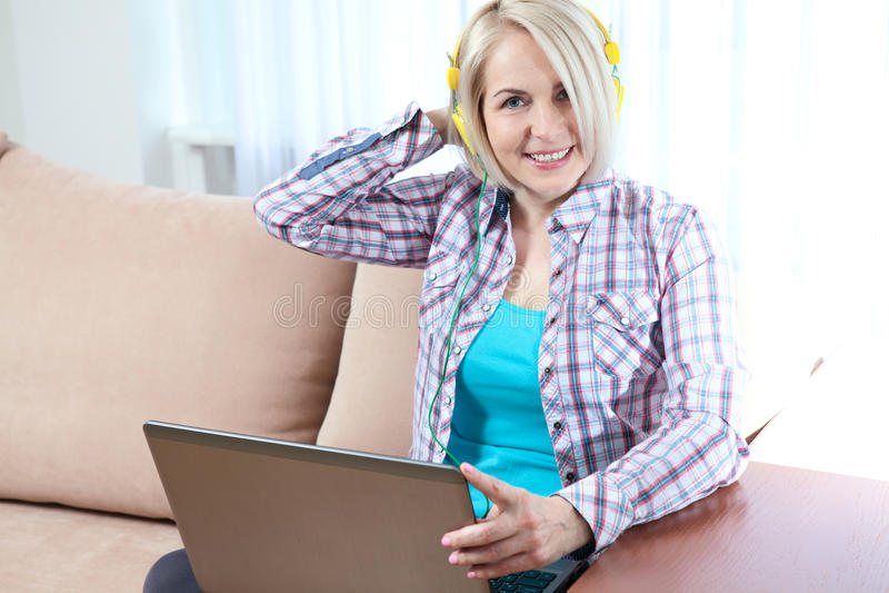 Mulher bonita no equipamento brilhante que aprecia a música em casa imagens de stock