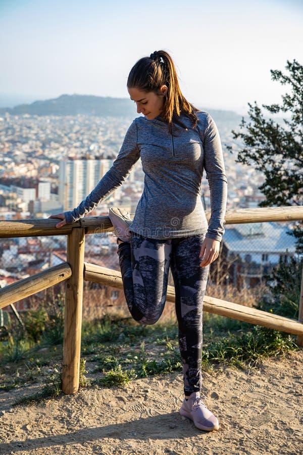A mulher bonita no equipamento do esporte que estica no parque com a cidade de Barcelona borrou no fundo imagem de stock royalty free