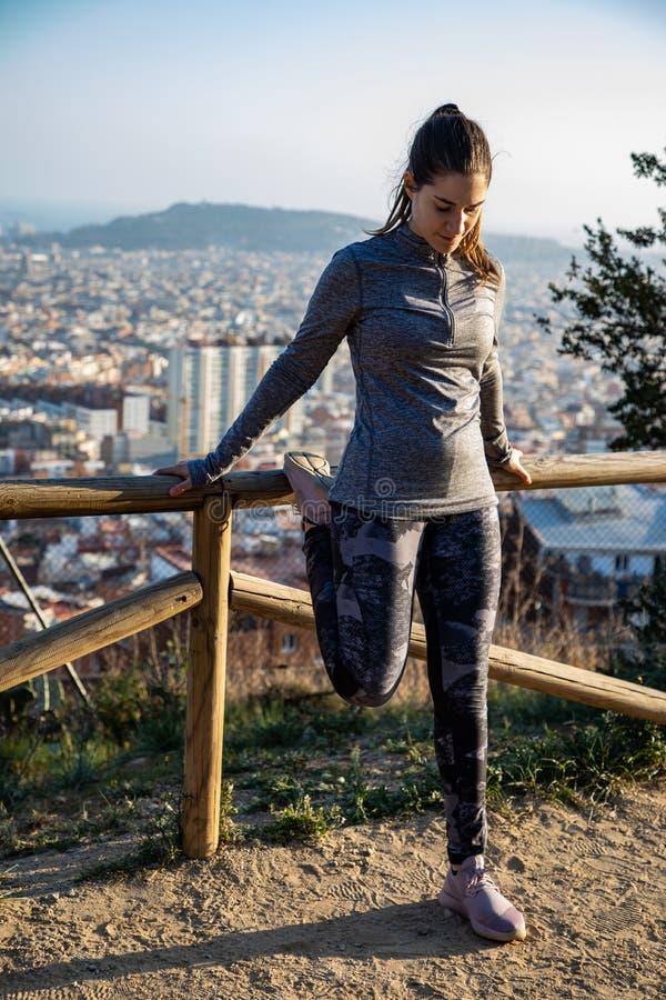 A mulher bonita no equipamento do esporte que estica no parque com a cidade de Barcelona borrou no fundo fotografia de stock royalty free