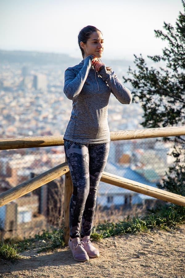 A mulher bonita no equipamento do esporte que estica no parque com a cidade de Barcelona borrou no fundo fotos de stock royalty free