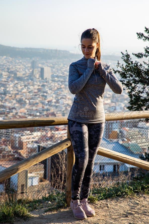 A mulher bonita no equipamento do esporte que estica no parque com a cidade de Barcelona borrou no fundo fotografia de stock
