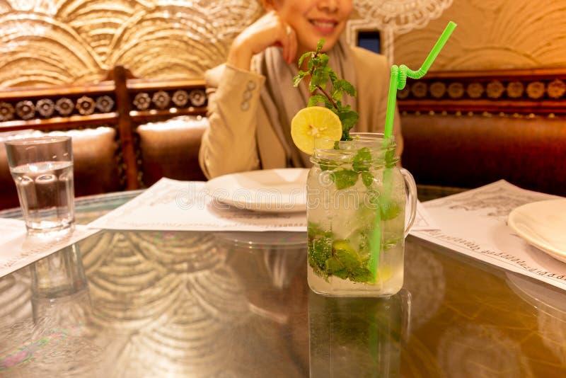 Mulher bonita no fundo que tem o cocktail fresco do mojito em um restaurante fotografia de stock royalty free