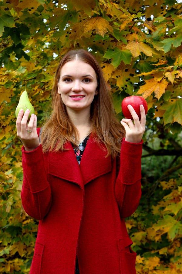 Mulher bonita no jardim com maçãs e pera fotografia de stock