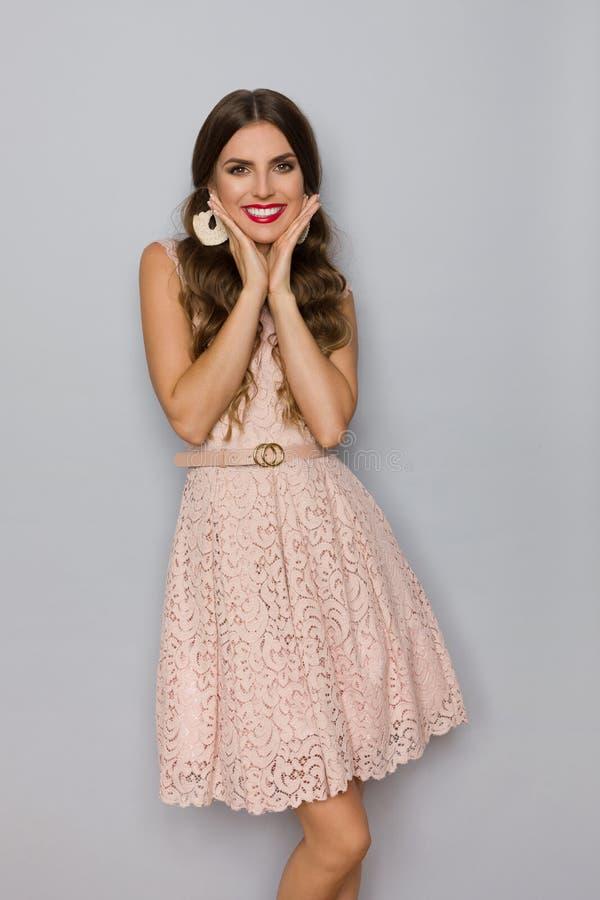 Mulher bonita no laço bege Mini Dress Is Holding Head nas mãos e no sorriso fotografia de stock