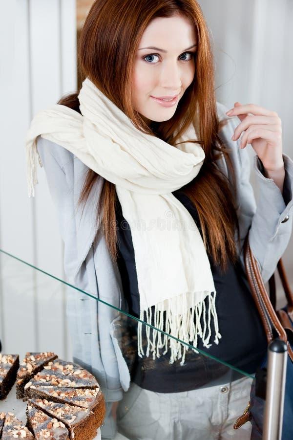 Mulher bonita no lenço que olha o indicador da padaria fotografia de stock royalty free