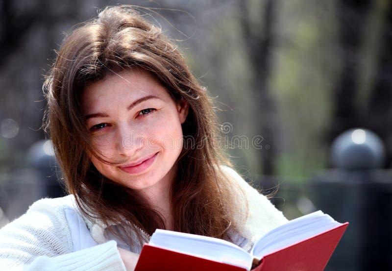 Mulher bonita no livro e no sorriso de leitura do parque imagens de stock