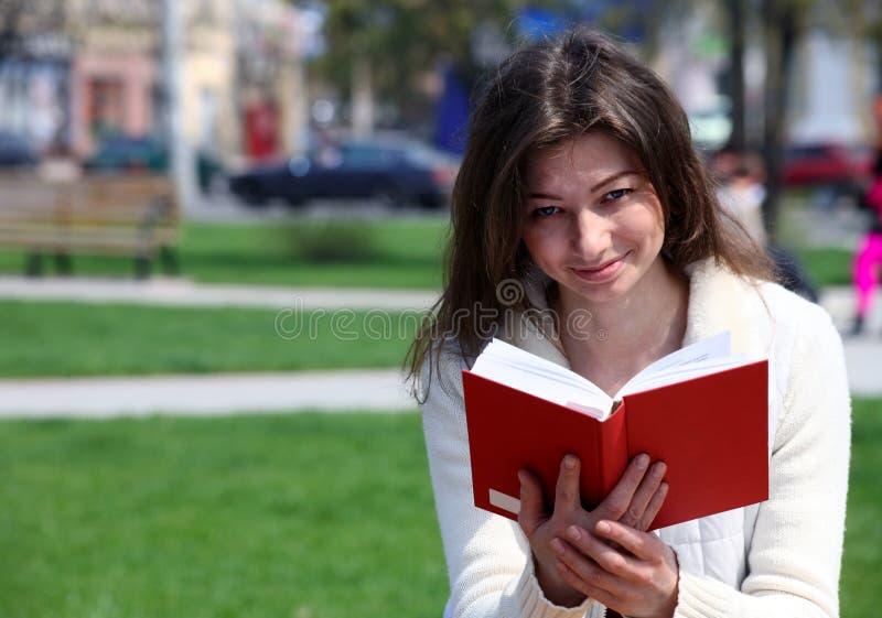 Mulher bonita no livro e no sorriso de leitura do parque imagem de stock