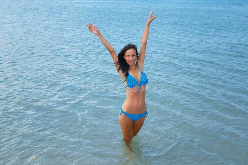 Mulher bonita no mar de turquesa no roupa de banho, conceito das férias fotos de stock royalty free