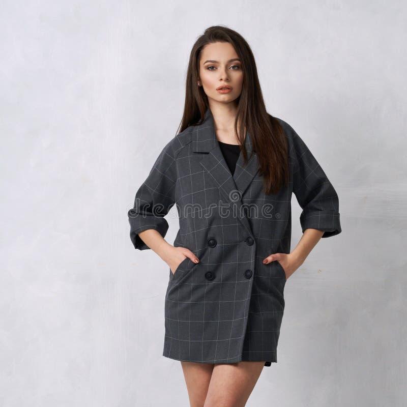 Mulher bonita no mini vestido cinzento com quatro botões fotos de stock