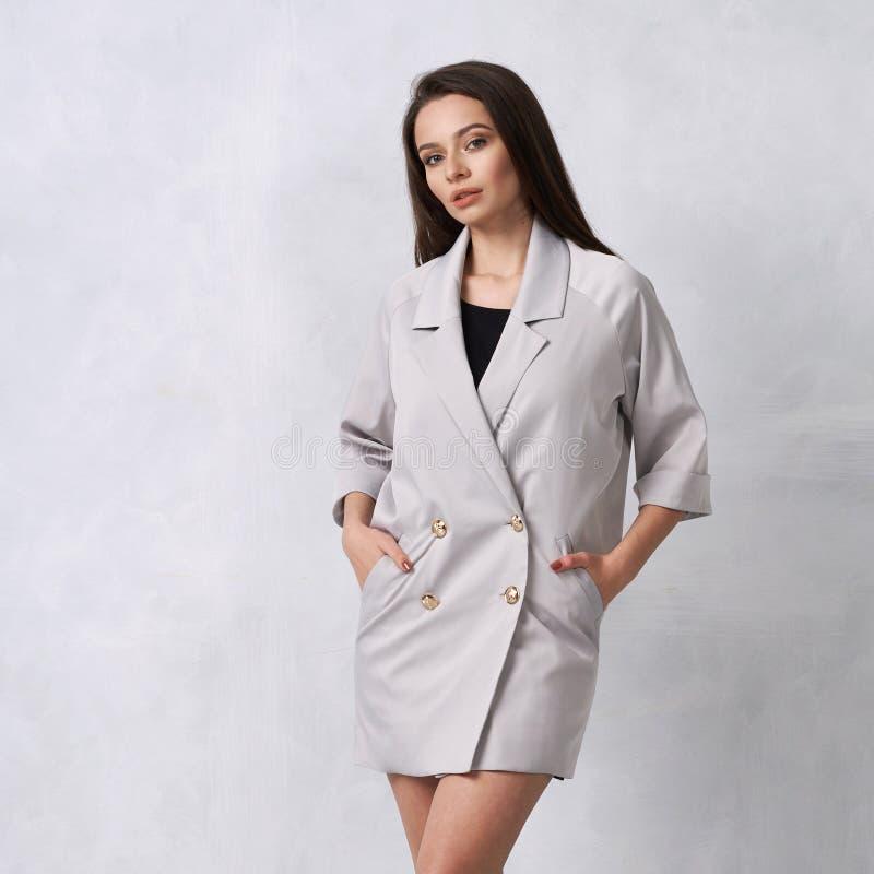 Mulher bonita no mini vestido cinzento com quatro botões imagens de stock
