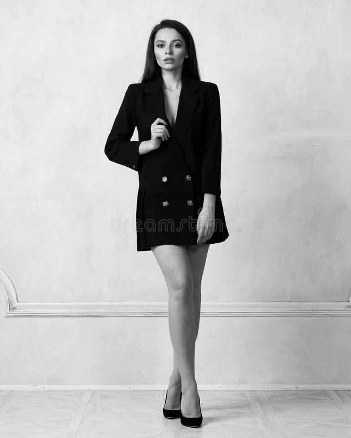 Mulher bonita no mini vestido preto com quatro botões fotografia de stock royalty free