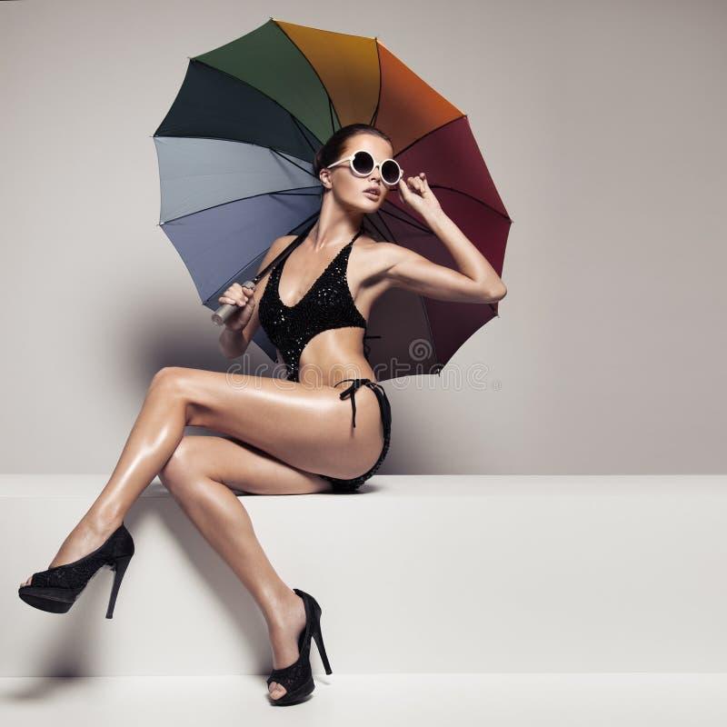 Mulher bonita no roupa de banho e óculos de sol que guardam o guarda-chuva fotos de stock royalty free