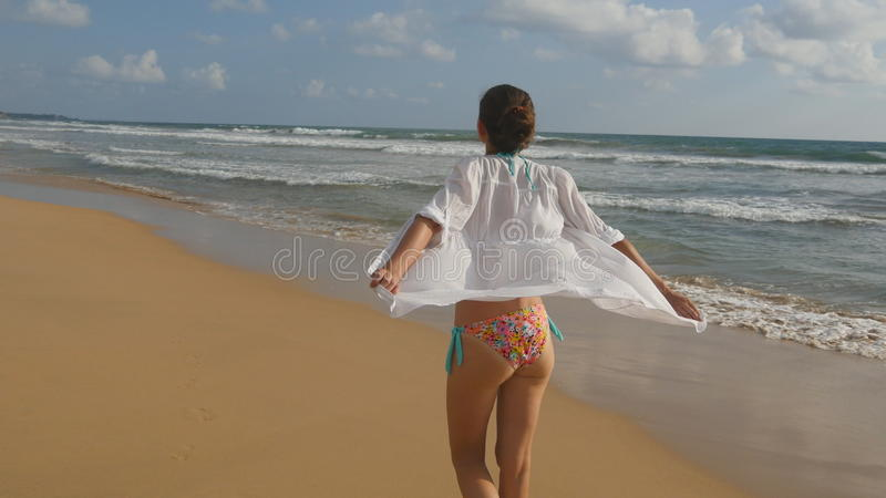 A mulher bonita no roupa de banho e a camisa que andam no mar encalham e levantaram as mãos Moça que vai na costa do oceano e foto de stock