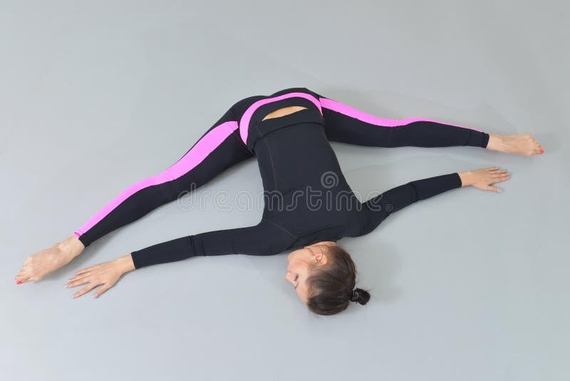 Mulher bonita no sportswear que exercita no estúdio da aptidão, executando a guita que encontra-se no assoalho Opinião de ângulo  foto de stock
