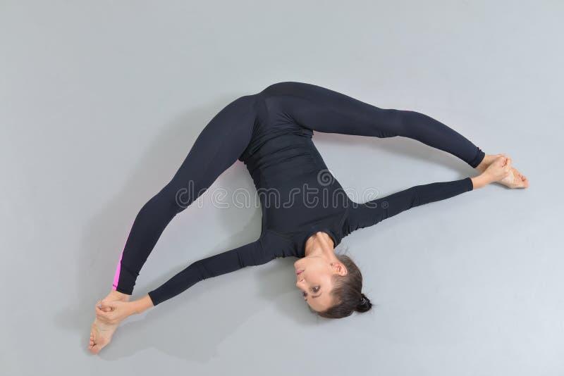 Mulher bonita no sportswear que exercita no estúdio da aptidão, executando a guita que encontra-se no assoalho Opinião de ângulo  fotos de stock