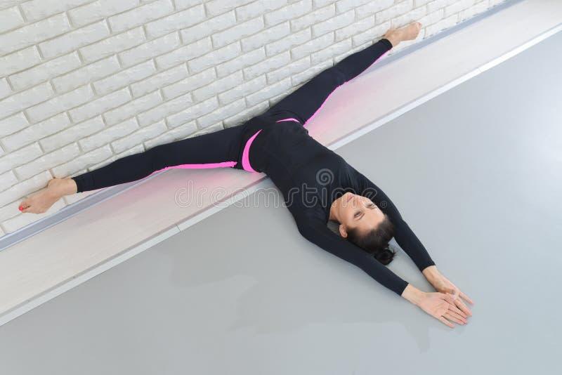 Mulher bonita no sportswear que exercita no estúdio da aptidão, executando a guita que encontra-se no assoalho perto da parede Ân imagens de stock