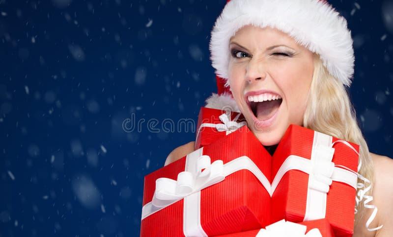 A mulher bonita no tampão do Natal guarda um grupo de presentes imagem de stock