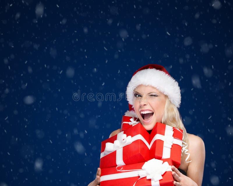 A mulher bonita no tampão do Natal guarda um grupo de presentes imagem de stock royalty free