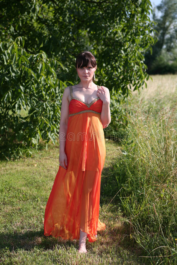 Mulher bonita no vestido alaranjado fotografia de stock