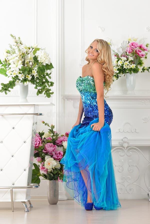 Mulher bonita no vestido azul no interior luxuoso. imagem de stock royalty free