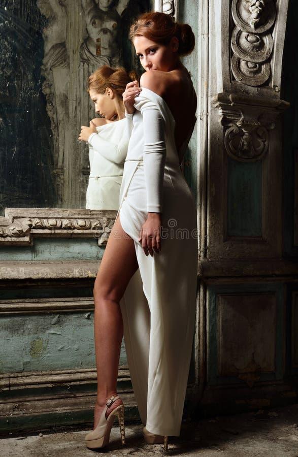 Mulher bonita no vestido branco com parte traseira despida. imagens de stock