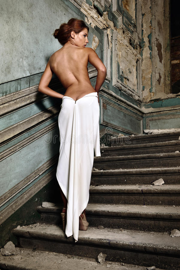 Mulher bonita no vestido branco com parte traseira despida no palácio. fotografia de stock royalty free