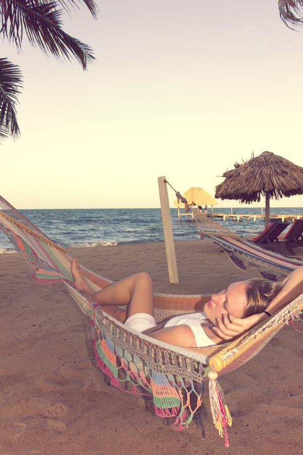 Mulher bonita no vestido branco na rede ao lado do oceano, retro imagem de stock royalty free