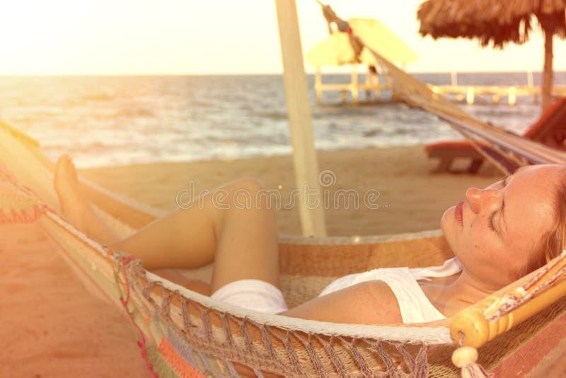 Mulher bonita no vestido branco na rede na praia ensolarada fotos de stock