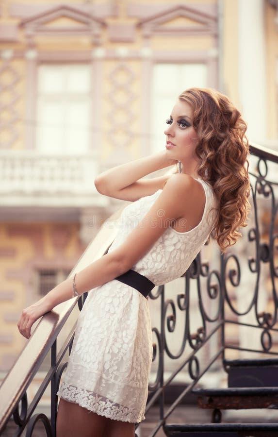 Mulher bonita no vestido branco nas escadas do metal foto de stock