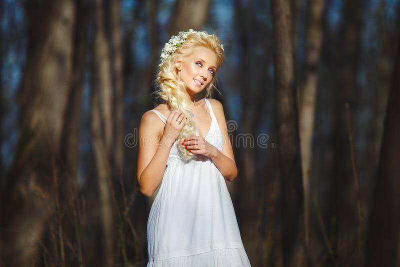 A mulher bonita no vestido branco puxa seu cabelo bonito no meio da floresta da mola imagens de stock royalty free
