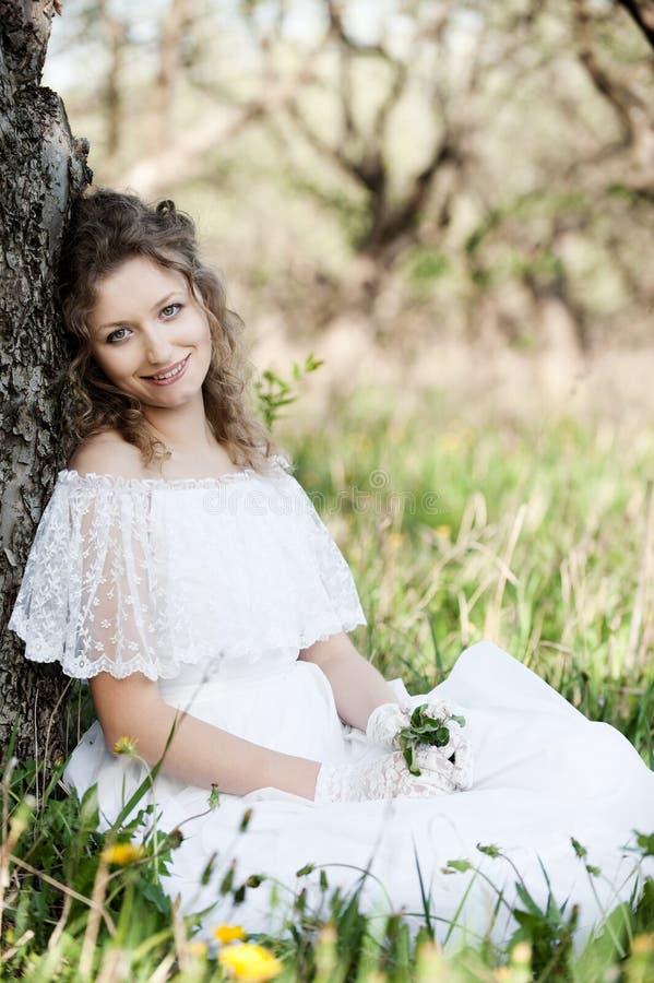 Mulher bonita no vestido branco que senta-se na grama fotos de stock