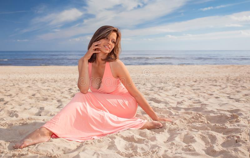 Mulher bonita no vestido cor-de-rosa no Sandy Beach fotos de stock