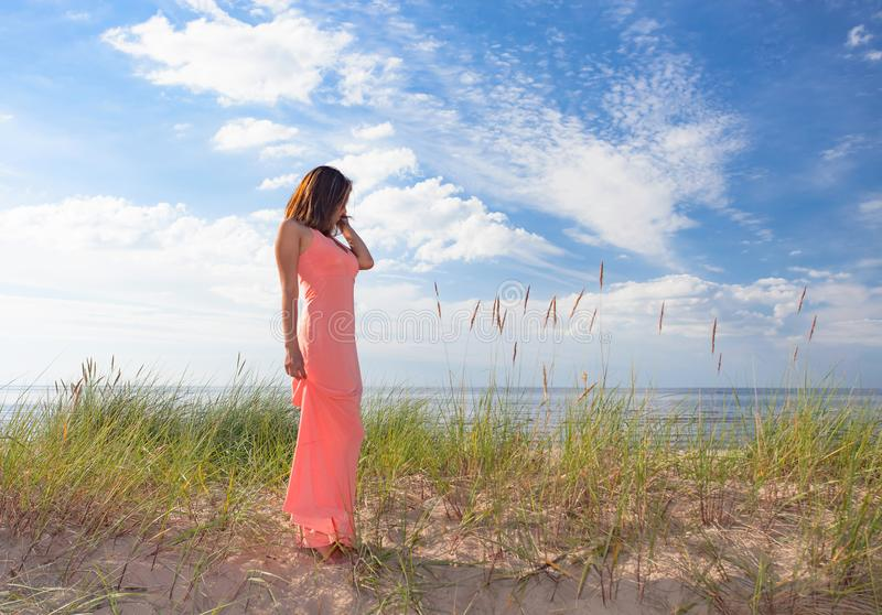 Mulher bonita no vestido cor-de-rosa no Sandy Beach fotografia de stock royalty free