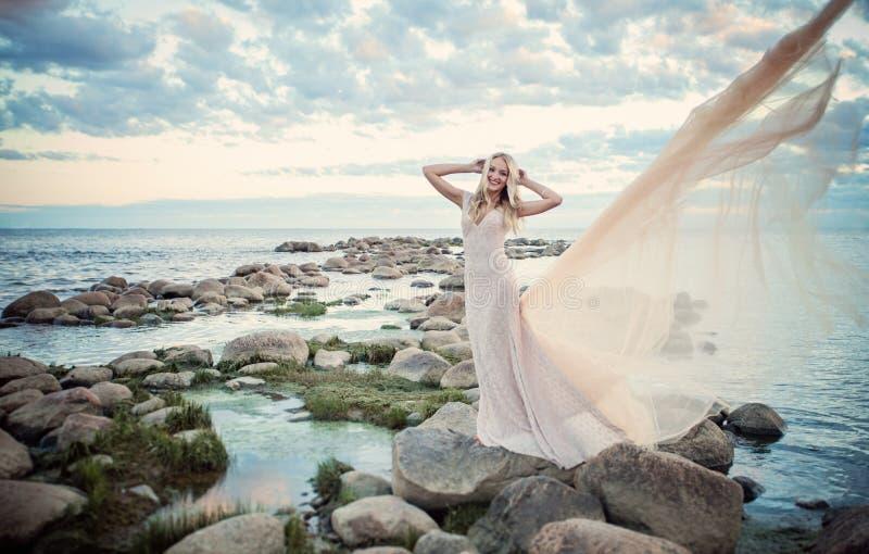 Mulher bonita no vestido de noite, no mar e no céu nebuloso fotografia de stock royalty free