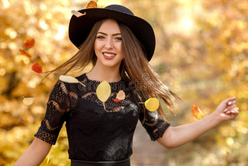 Mulher bonita no vestido e no chapéu pretos no outono fotografia de stock royalty free