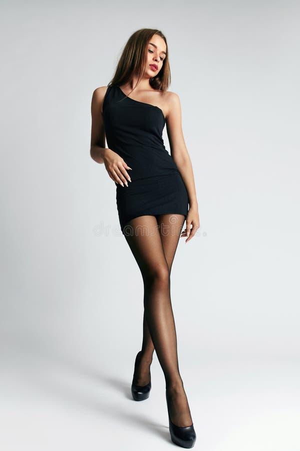 Mulher bonita no vestido e em meias pretos fotografia de stock royalty free