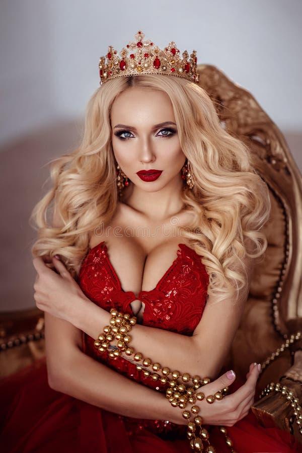 Mulher bonita no vestido e na coroa vermelhos rainha Retrato imagens de stock