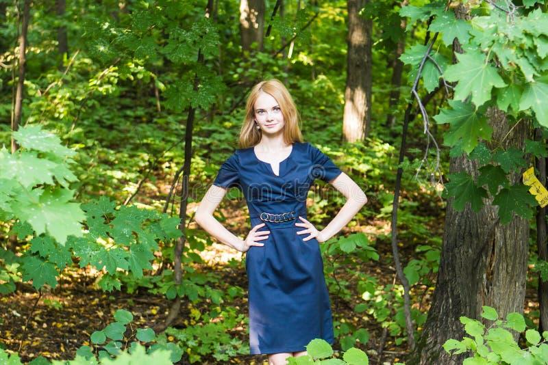 Mulher bonita no vestido elegante e no sorriso encantador que levantam no parque A menina do negócio anda após o trabalho imagem de stock