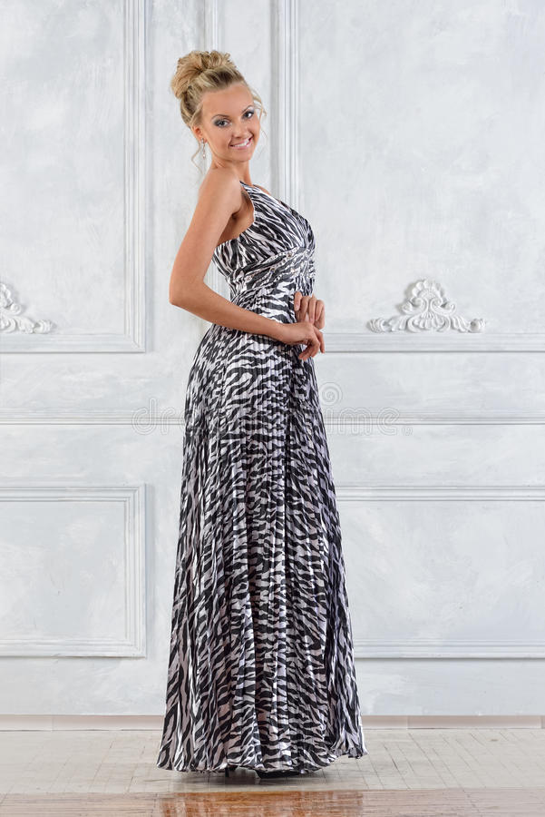 Mulher bonita no vestido longo lilás no interior branco. imagens de stock