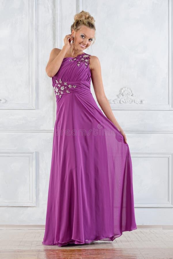 Mulher bonita no vestido longo lilás no interior branco. fotos de stock royalty free