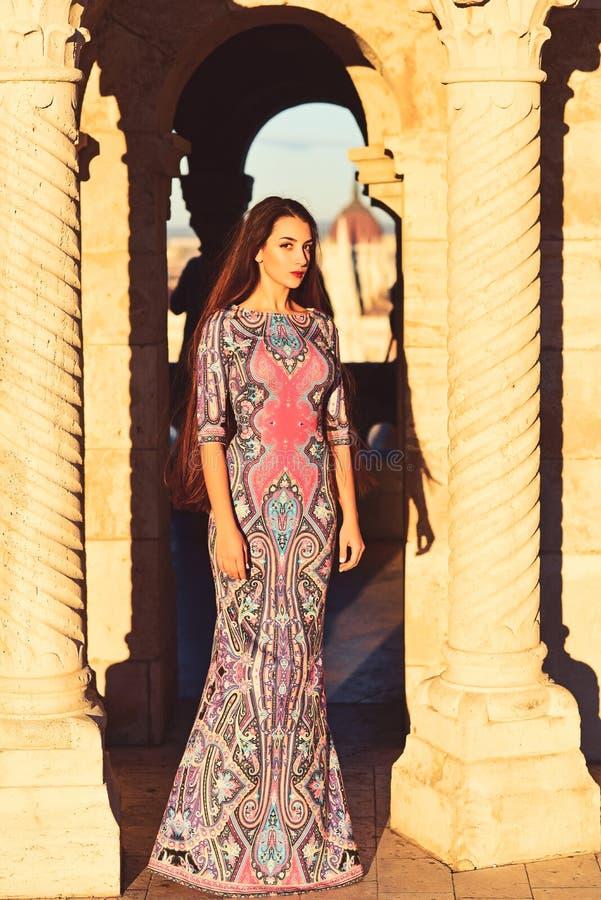 Mulher bonita no vestido longo que levanta perto da coluna antiga Arquitetura maravilhosa imagem de stock